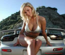 blonde model sitting on top of a sports car