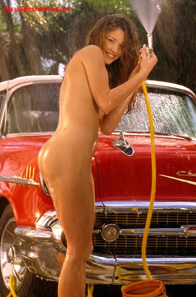Sexy Brunette model with lovely body next to a classic Chevrolet Convertible.