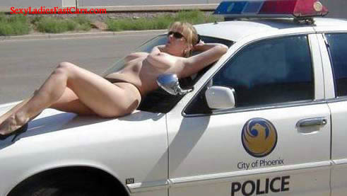 Sexy model laying out on a police car topless, sun bathing.