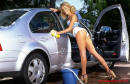 Pretty blonde girl washing her foriegn car.